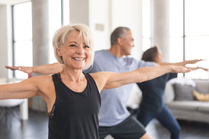 A multi-ethnic group of seniors is attending a fitness class. They are indoors. The group is doing yoga. The individual in focus is a a beautiful and fit caucasian woman. She is smiling directly at the camera.